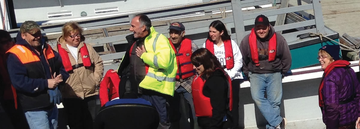 people smiling while wearing a PFD on a fishing boat